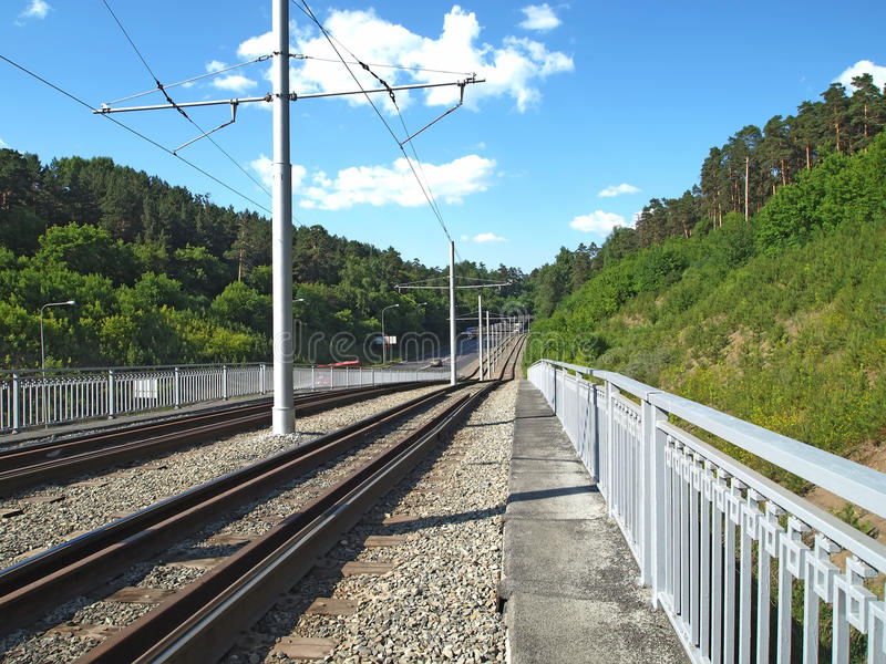 Tram tracks go in and gave to the horizon. Line of rails, road, mountains with pine forest, railway royalty free stock photography