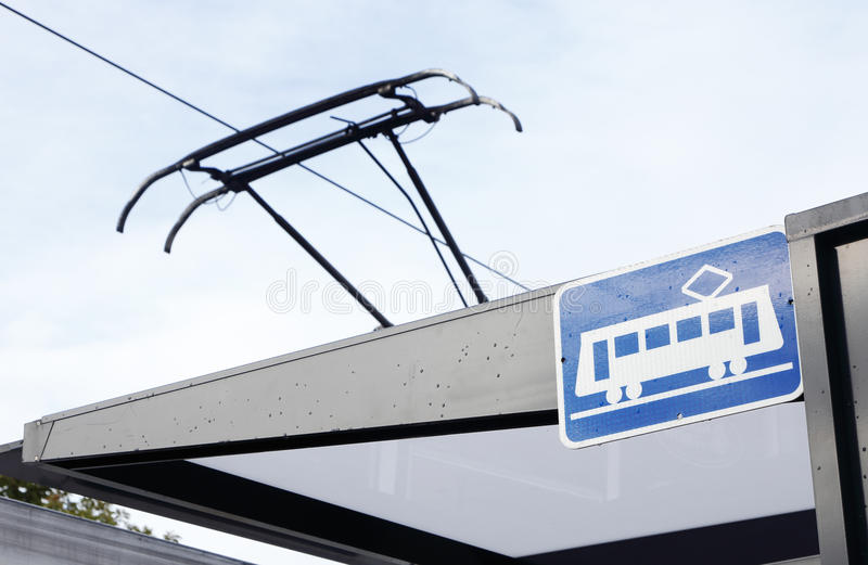 Tram at tram stop. A tram stop with tram stop sign and the pantograph of an electric powered tram visible royalty free stock photo