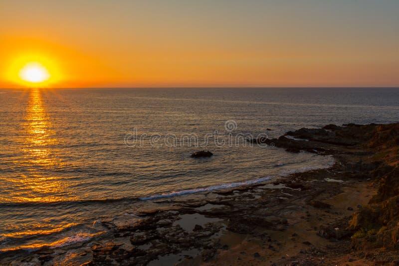 Tramonto ad una spiaggia rocciosa in Pomos, Cipro immagine stock libera da diritti