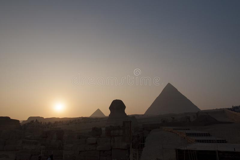 Tramonto alla Sfinge ed alle grandi piramidi dell'Egitto immagini stock libere da diritti