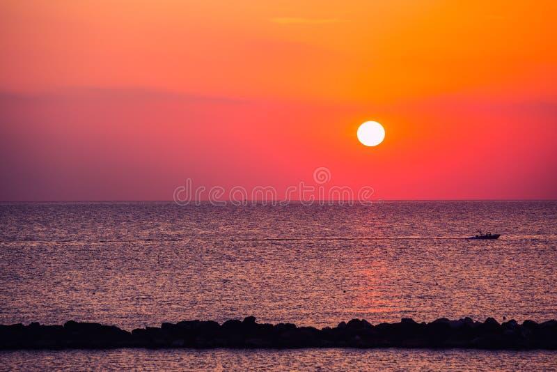 Tramonto alla spiaggia con la barca ed il mare fotografia stock libera da diritti