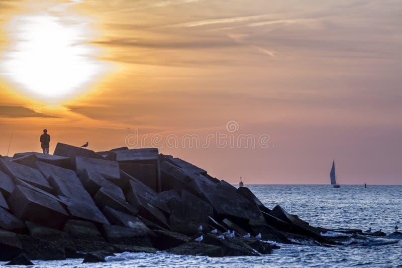 Tramonto alla spiaggia rocciosa L'aia di Scheveningen fotografia stock