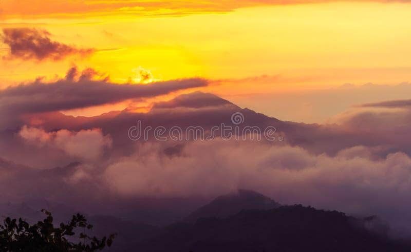 Tramonto arancio nebbioso nelle montagne immagine stock