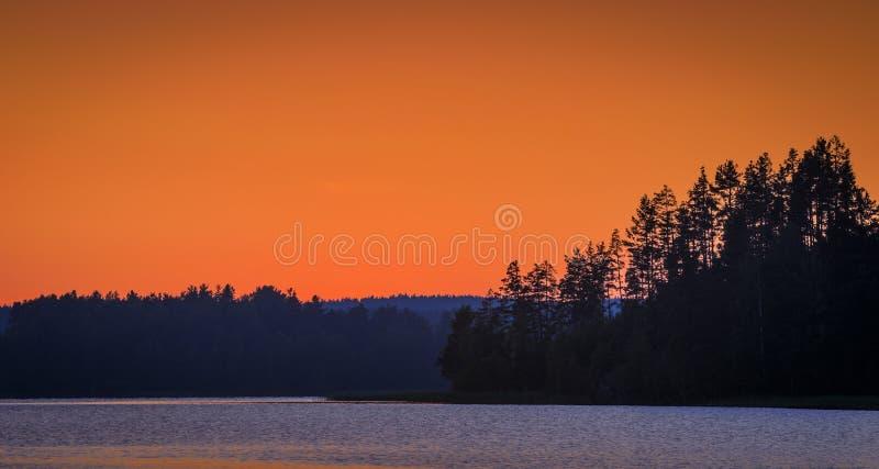 Tramonto arancione sopra il lago fotografie stock