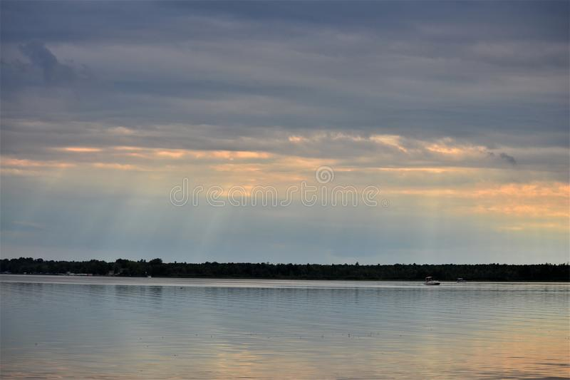 Tramonto attraverso i cieli nuvolosi sopra il lago Shawano in Wisconsin fotografia stock libera da diritti