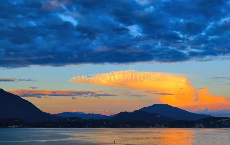 Tramonto blu variopinto con le nuvole arancio e vista naturale del paesaggio sul lago Maggiore, Italia fotografie stock