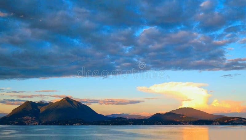 Tramonto blu variopinto con le nuvole arancio e vista naturale del paesaggio sul lago Maggiore, Italia immagini stock libere da diritti