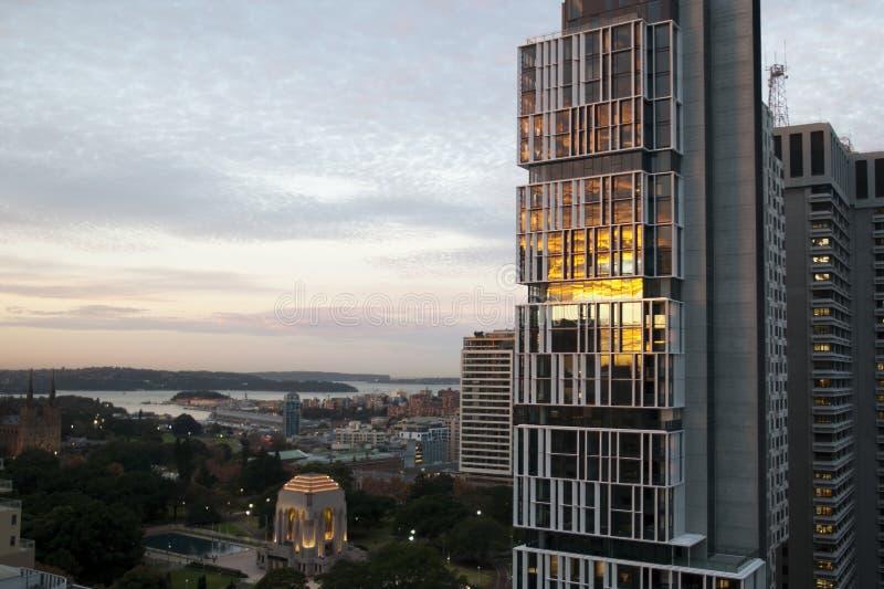 Tramonto che riflette in vetro di grattacielo di appartamento con Anzac Memorial in Hyde Park ed in porto nei precedenti fotografie stock libere da diritti