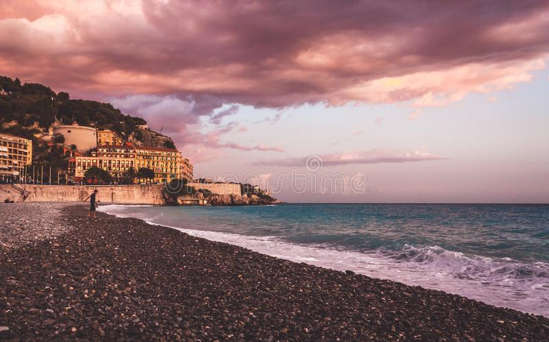 Tramonto colorato viola sulla spiaggia di Nizza fotografia stock libera da diritti