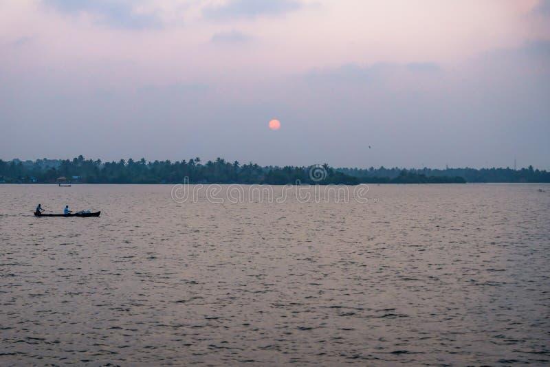 Tramonto con barca da pesca al lago Ashtamudi, Kollam, Kerala, India immagine stock