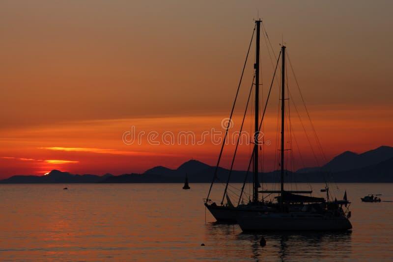 Tramonto con la siluetta dell'yacht fotografia stock libera da diritti