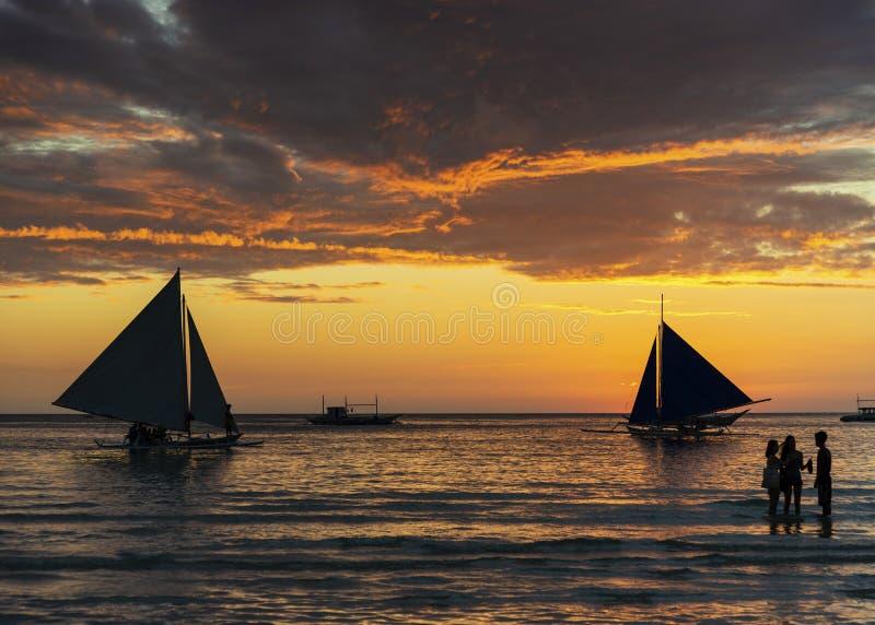 Tramonto con le barche a vela ed i turisti nel philipp dell'isola di boracay fotografia stock