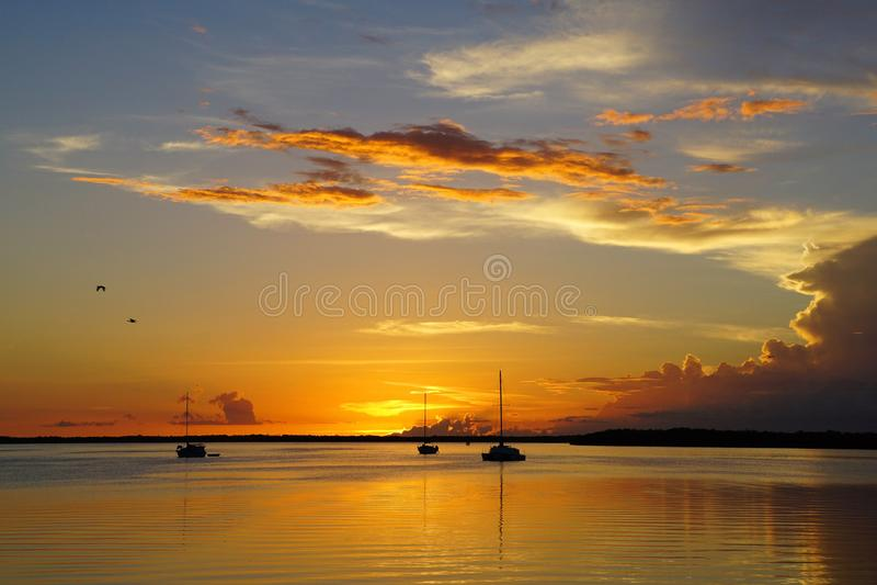 Tramonto con tre barche a vela ancorate nell'oceano fotografia stock libera da diritti