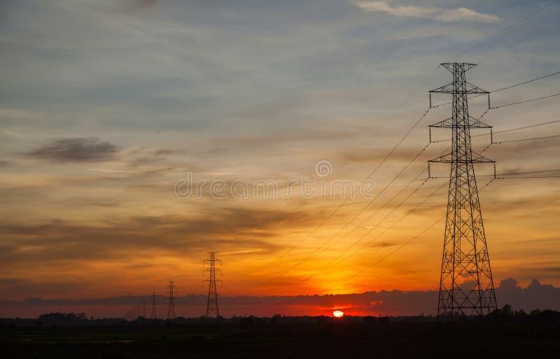 Tramonto contro l'alto palo di corrente elettrica fotografia stock