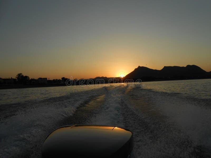 Tramonto da un'imbarcazione a motore, Fateh Sagar Lake, Udaipur, Ragiastan fotografie stock libere da diritti