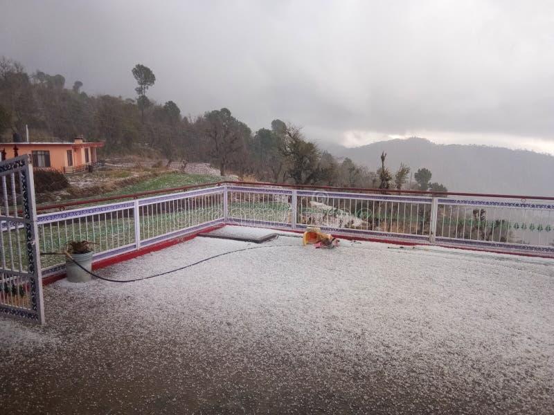 Tramonto dal tetto della casa con la caduta della neve fotografia stock libera da diritti
