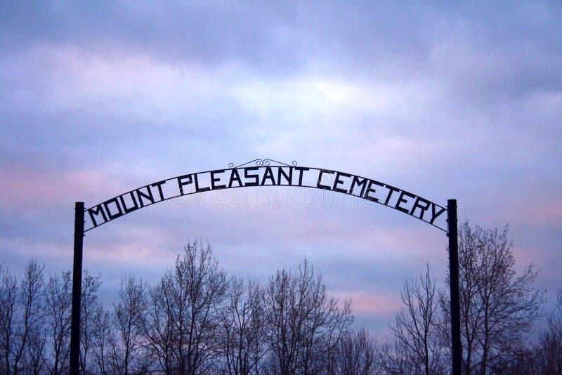Tramonto del blu di rosa dell'arco del ferro battuto del segno del cimitero immagini stock
