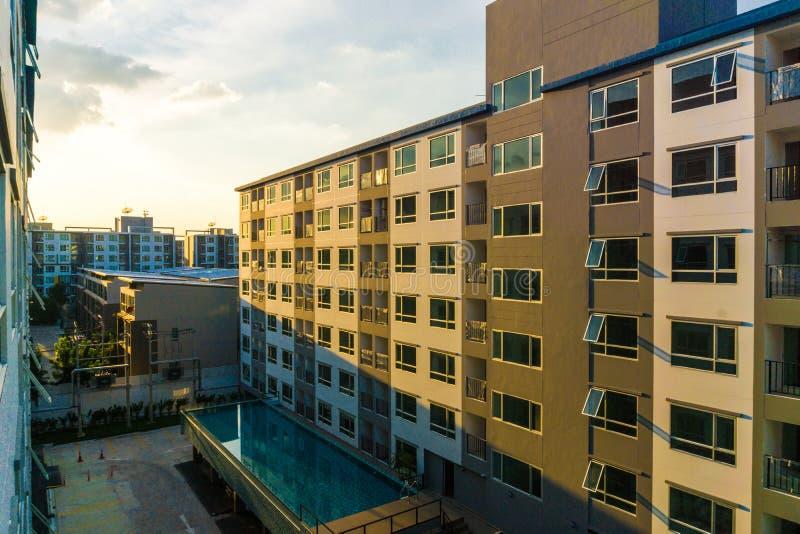 Tramonto del condominio con gli appartamenti moderni del nuovo blocchetto della piscina fotografie stock