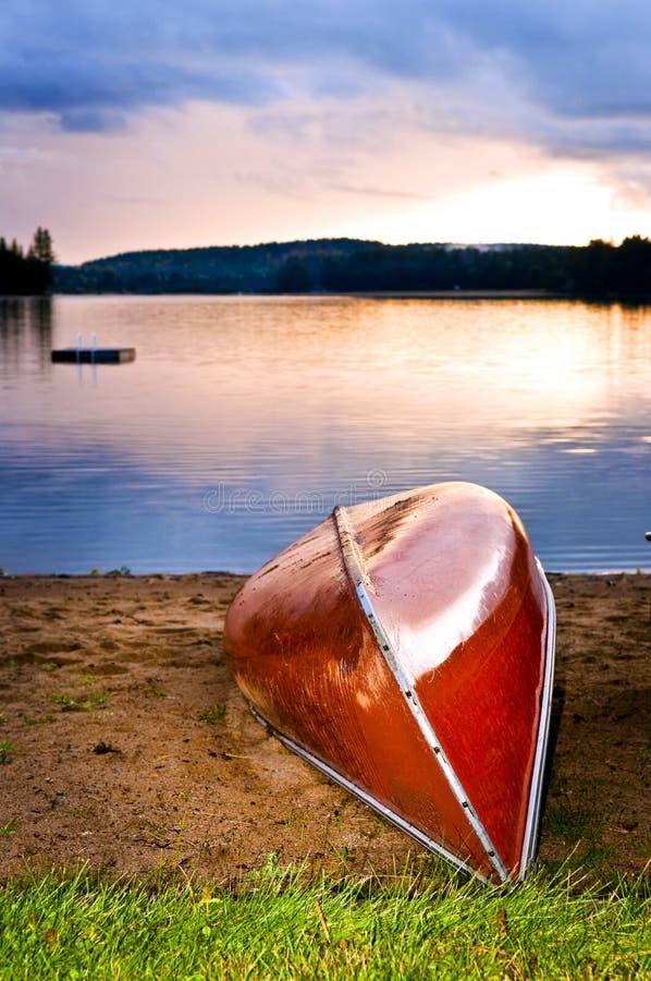 Tramonto del lago con la canoa sulla spiaggia immagini stock