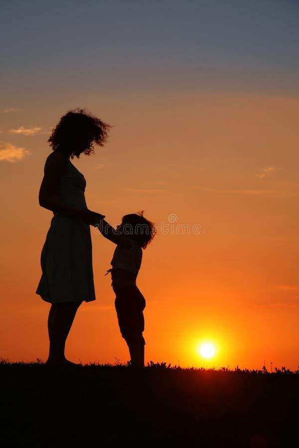 tramonto della siluetta della madre della figlia immagine stock libera da diritti