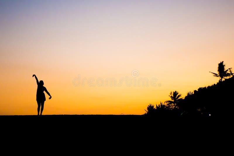 Tramonto della spiaggia di Sanur della siluetta della ragazza di dancing di Bali fotografia stock