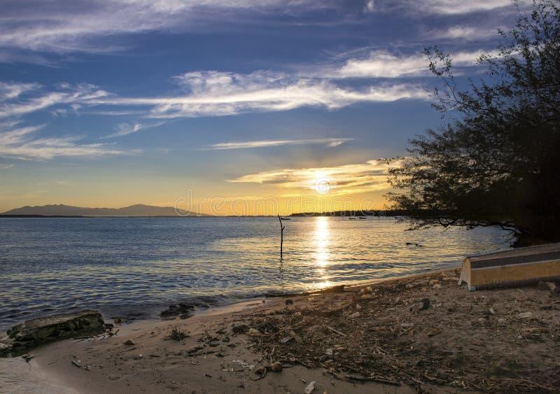 Tramonto di alba alla spiaggia dell'isola con inquinamento immagini stock
