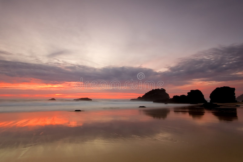 Tramonto di colore rosso della spiaggia di Adraga fotografie stock