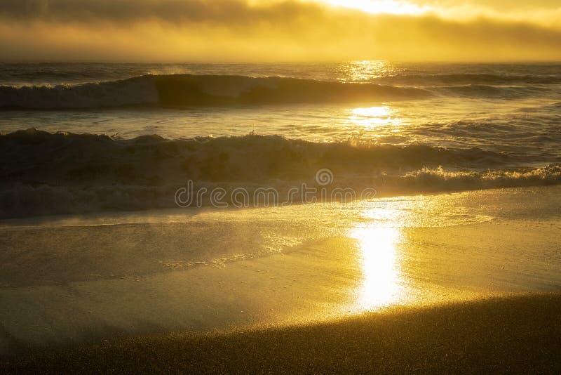 Tramonto di estate sopra l'oceano e la spiaggia immagine stock