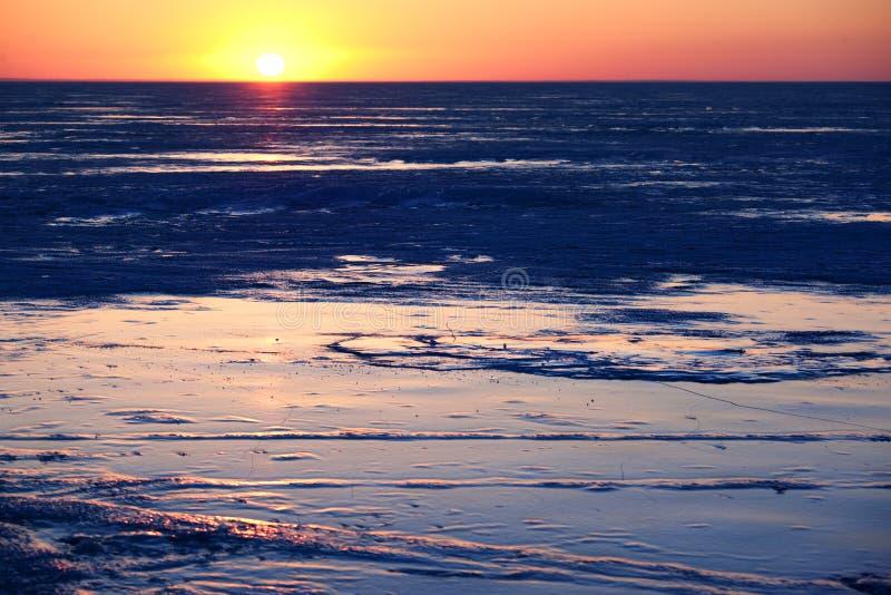 Tramonto di inverno sul ghiaccio del lago fotografia stock libera da diritti