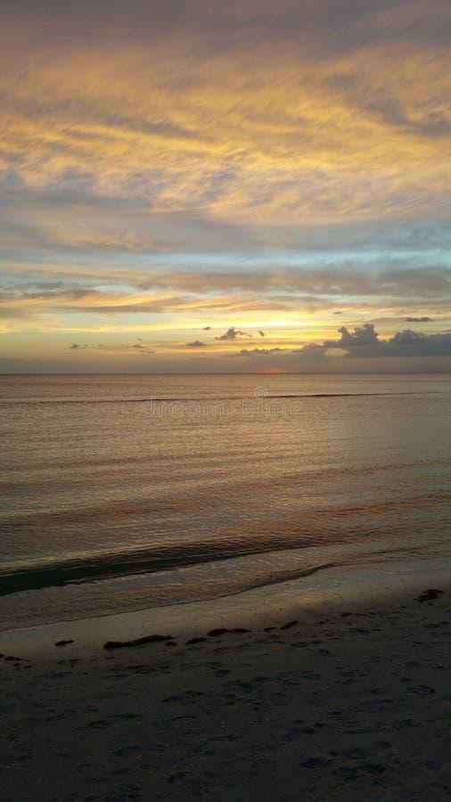 Tramonto di Napoli Florida ed onde calmanti, fotografia stock libera da diritti