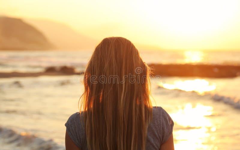 Tramonto di sorveglianza della giovane donna alla spiaggia, guardante al mare, montagne nella distanza Vista dalla parte posterio fotografie stock
