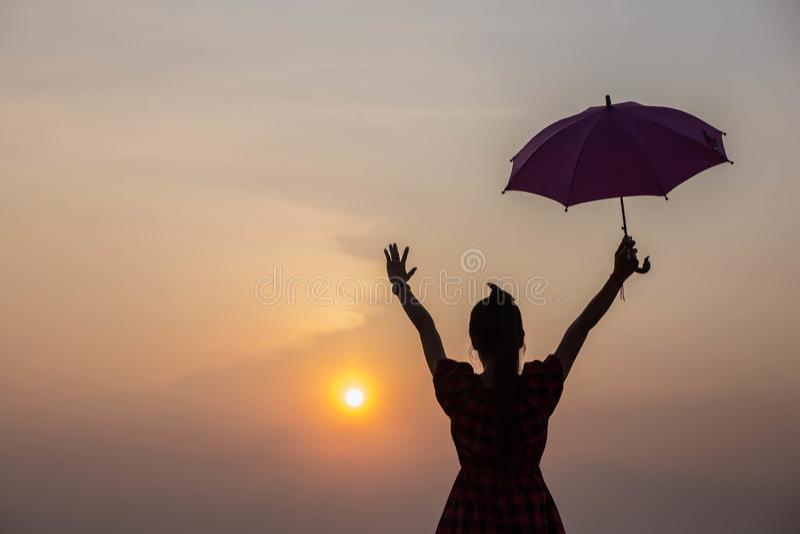 Tramonto di sorveglianza della ragazza che tiene un ombrello di spiaggia fotografie stock