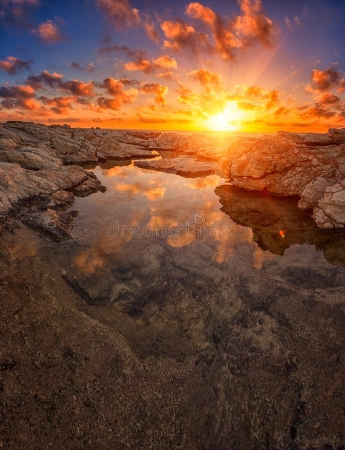Tramonto di stupore sulle rocce bianche con il sole, il cielo blu, le nuvole e la riflessione nell'acqua, Cipro fotografia stock