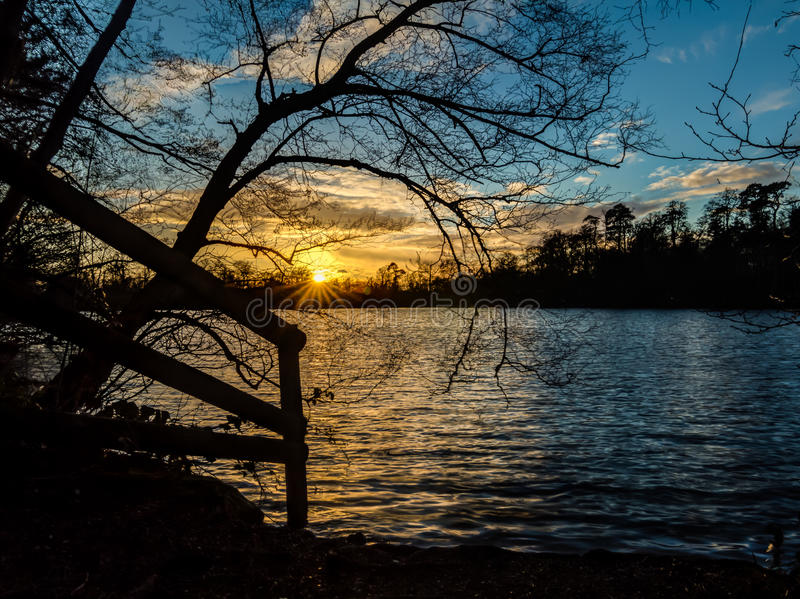 Tramonto dietro il lago fotografia stock