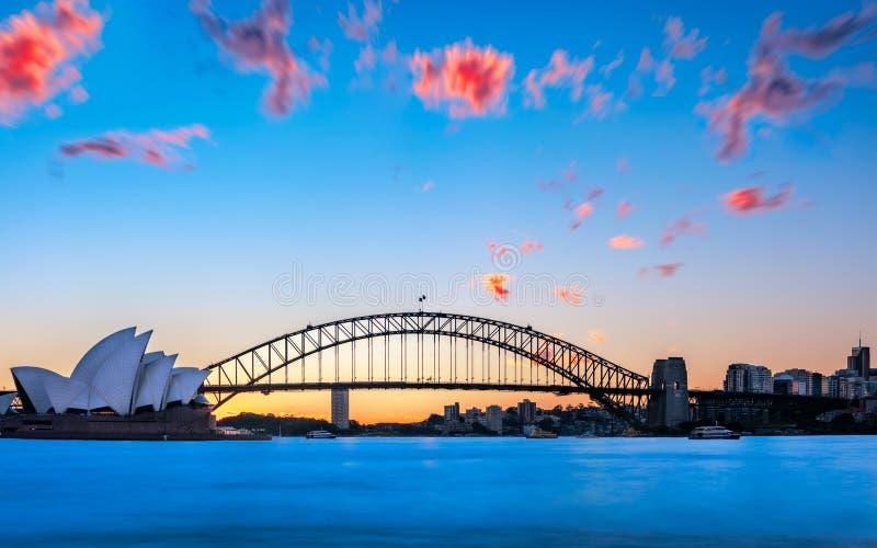 Tramonto dietro il teatro dell'opera e Sydney Harbour Bridge immagine stock libera da diritti