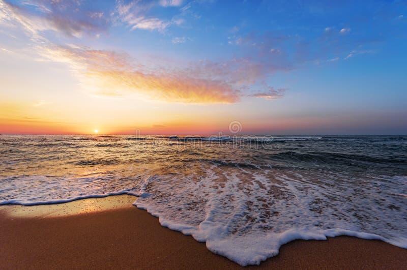 Tramonto dorato di alba sopra il mare immagine stock