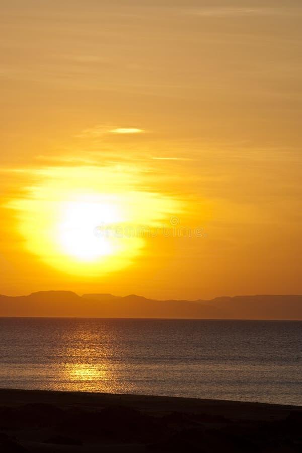 Tramonto dorato sopra l'orizzonte della montagna e della spiaggia immagini stock