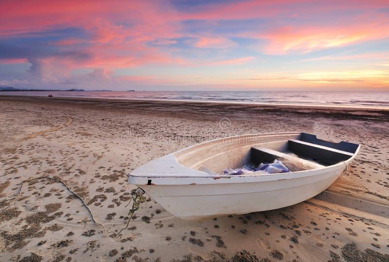 Tramonto drammatico e una barca fotografia stock
