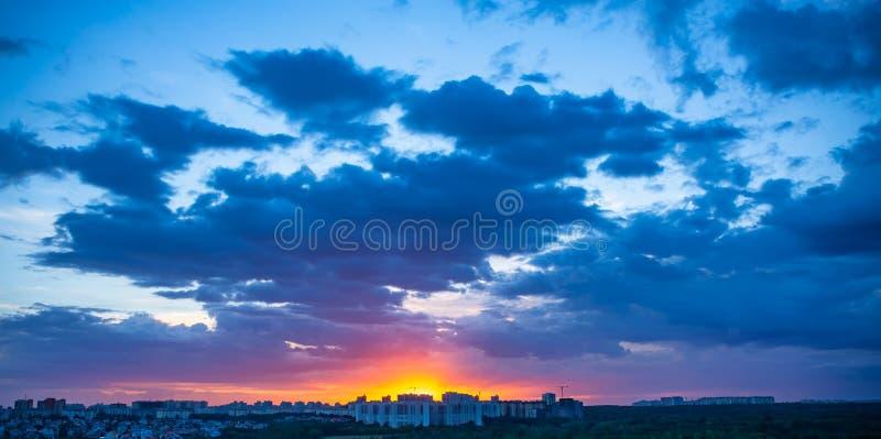 Tramonto drammatico sopra la città di sera con le nuvole ed il cielo blu luminosi, bello panorama fotografia stock libera da diritti
