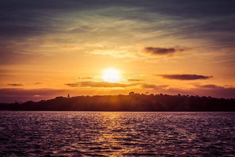 Tramonto drammatico sopra le acque calme della baia con la costa collinosa alla distanza fotografie stock