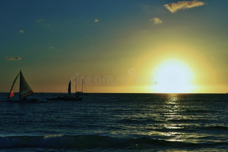 Tramonto e barche a vela nell'isola di Boracay con il cielo blu ed arancio fotografia stock libera da diritti