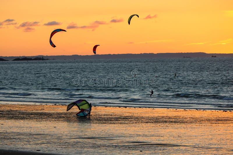 Tramonto e Kitesurfers sulla spiaggia in Saint Malo, Bretagna, Francia fotografia stock libera da diritti