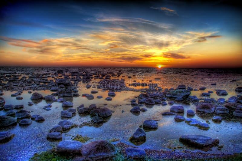 Tramonto e pietre del mare fotografia stock