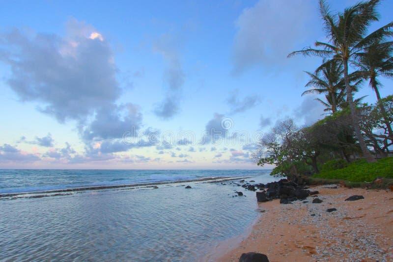 Tramonto e riflessione rosa e blu sull'acqua dell'oceano al ` di Kapa rive in Kauai, Hawai immagine stock