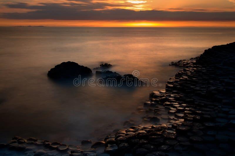 Tramonto e rocce costiere a forma di uniche alla strada soprelevata di Giants, Irlanda del nord fotografia stock