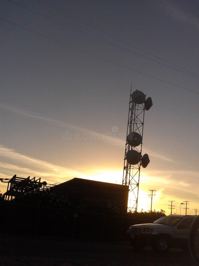 Tramonto e una vista di una torre di comunicazioni immagini stock