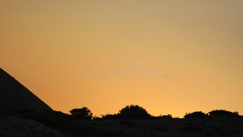 Tramonto giallo opaco nelle rocce del mare adriatico immagini stock
