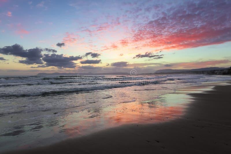 Tramonto incantevole Mare di tempesta con le alte onde Blu incredibili, rosa, colori arancio del cielo sono riflessi sulla sabbia immagini stock libere da diritti