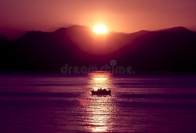 Tramonto, lago che scintilla Pescatori che conducono un piccolo peschereccio nella pesca fotografie stock