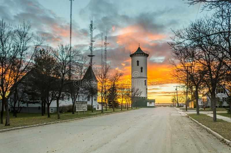 Tramonto luminoso e variopinto nella cittadina con la torre e chiesa immagine stock libera da diritti